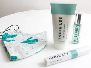 skin care routine for maskne featuring Indie Lee Clearing Mask, Indie Lee Banish Stick, Verdura naturalternative Blue Fairy Concentrate, and a cotton mask